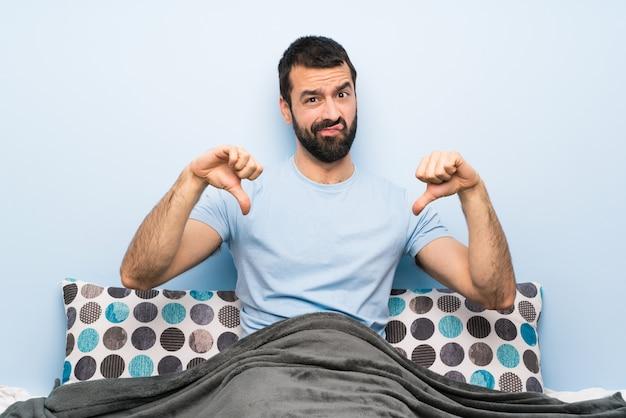 Mężczyzna w łóżku pokazuje kciuka puszek