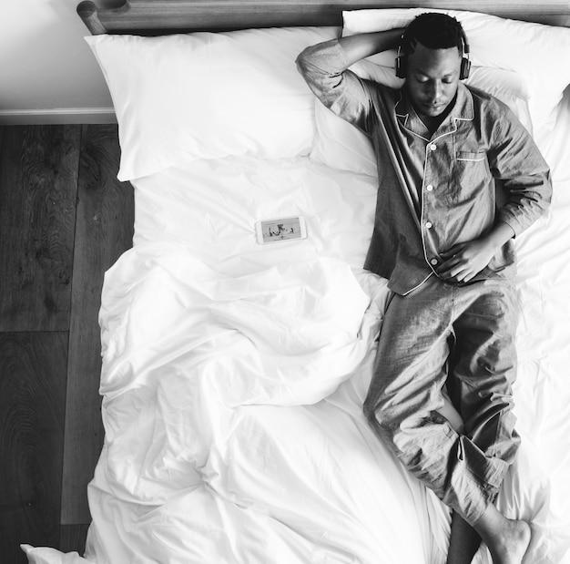 Mężczyzna w łóżku słucha muzyka