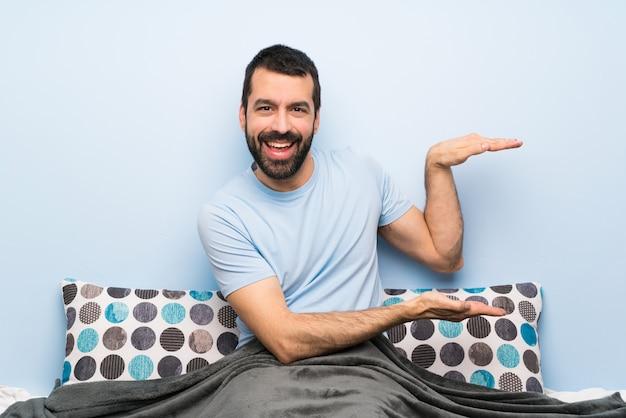 Mężczyzna w łóżku trzyma copyspace, aby wstawić reklamę