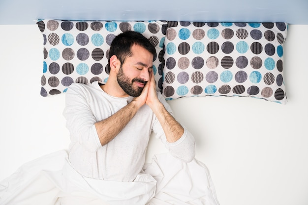 Mężczyzna w łóżku w odgórnym widoku robi sen gestowi w dorable wyrażeniu