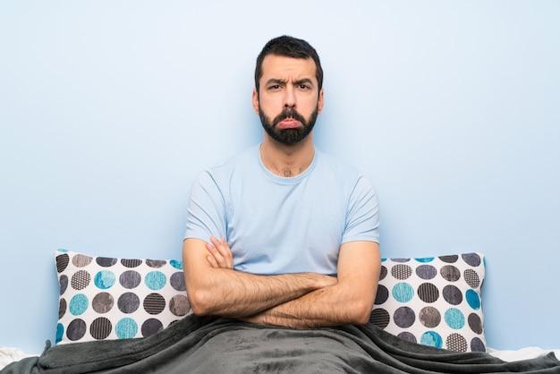 Mężczyzna w łóżku z smutnym i przygnębionym wyrazem