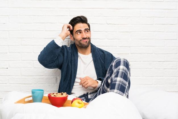 Mężczyzna w łóżku z szlafrokiem i po śniadaniu mając wątpliwości i myląc wyraz twarzy