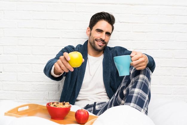 Mężczyzna w łóżku z szlafrokiem i po śniadaniu