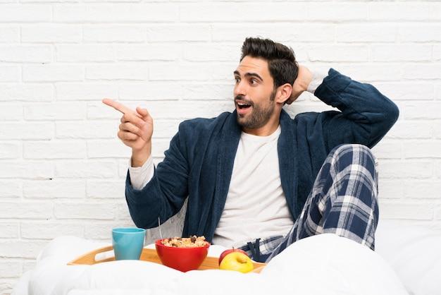 Mężczyzna w łóżku z szlafrokiem i śniadanie zaskoczony i wskazując palcem na bok