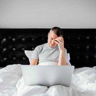 Mężczyzna w łóżku za pomocą laptopa