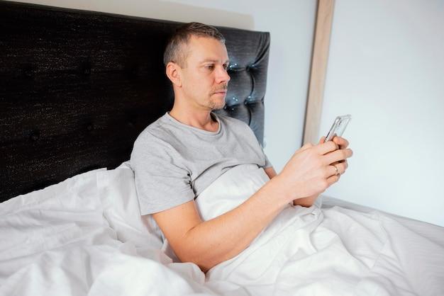 Mężczyzna w łóżku za pomocą telefonu komórkowego