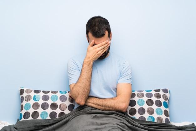 Mężczyzna w łóżku zakrywający oczy rękami. nie chcę czegoś widzieć