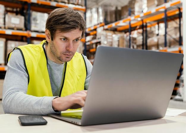 Mężczyzna w magazynie pracuje na laptopie