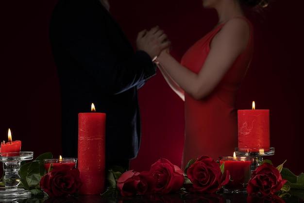 Mężczyzna w marynarce i kobieta w czerwonej sukience trzymają się za ręce świece i luksusowe róże