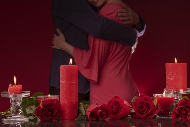 Mężczyzna w marynarce i kobieta w różowej sukience tańczą przytulając się świece i luksusowe róże