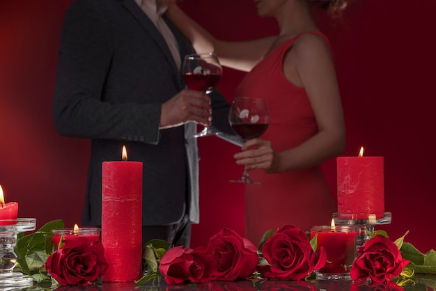 Mężczyzna w marynarce i kobieta w różowej sukience trzymają okulary tańczą, przytulają się