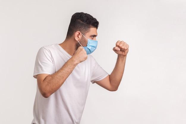 Mężczyzna w masce chirurgicznej uderzający pięścią, boksujący z zaciśniętymi pięściami, walczący z chorobą zakaźną