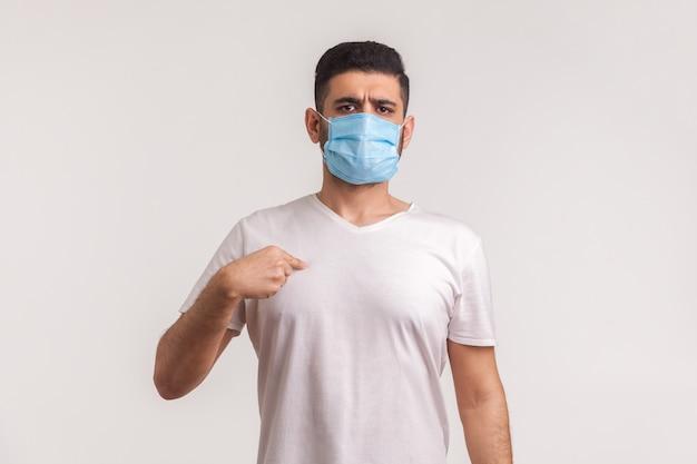 Mężczyzna w masce chirurgicznej, wskazujący na siebie, noszący filtr ochronny, aby zapobiec zakażeniu koronawirusem