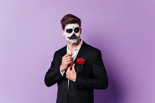 Mężczyzna w masce czaszki mruga zalotnie, pozuje z nałożonymi wąsami do portretu na odosobnionym tle.