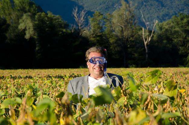 Mężczyzna w masce do nurkowania stojący w polu upraw