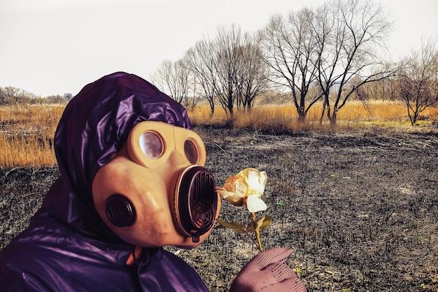 Mężczyzna w masce gazowej trzyma kwiat. wpływ promieniowania. zanieczyszczenie środowiska. niebezpieczna energia jądrowa. katastrofa ekologiczna.natura płonie. spalone lasy. puste pole.