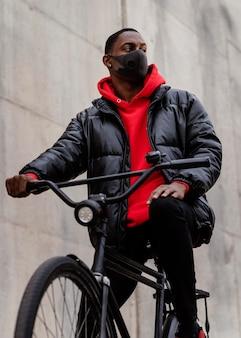 Mężczyzna w masce i jeżdżący na rowerze