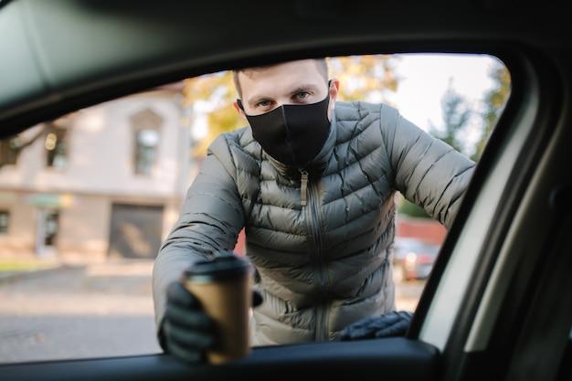 Mężczyzna w masce i rękawiczkach ochronnych przynosi kierowcy kawę.