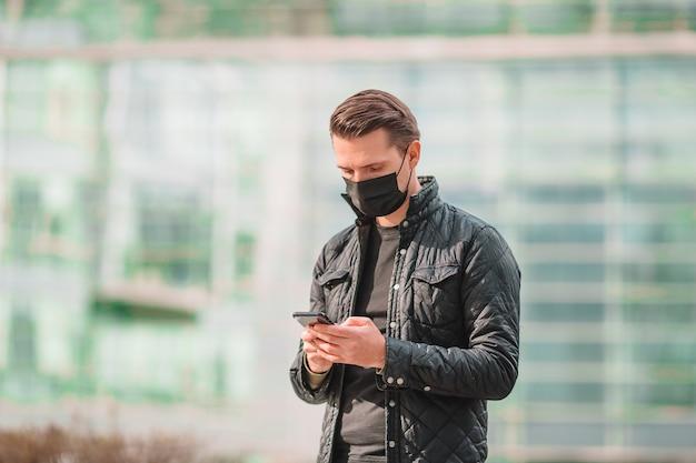 Mężczyzna w masce i za pomocą smartfona na ulicy