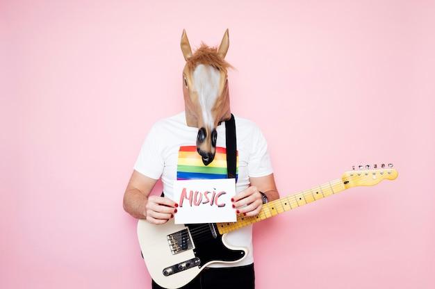 Mężczyzna w masce konia trzyma plakat z muzyką
