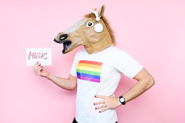 Mężczyzna w masce konia trzymający plakat z różową muzyką