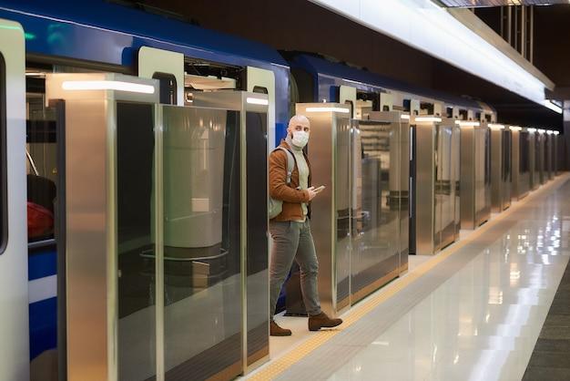Mężczyzna w masce medycznej, aby uniknąć rozprzestrzeniania się koronawirusa, trzyma smartfon, wychodząc z nowoczesnego wagonu metra