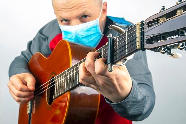 Mężczyzna w masce medycznej gra na gitarze klasycznej na białym tle