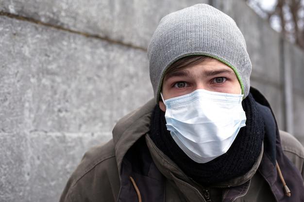 Mężczyzna w masce medycznej, ochrona przed grypą, koronawirusem i innymi wirusowymi przeziębieniami.
