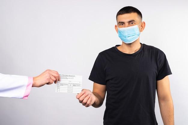 Mężczyzna w masce medycznej otrzymuje od lekarza kartę szczepień