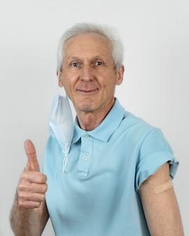 Mężczyzna w masce medycznej pokazujący kciuki do góry z bandażem na ramieniu po szczepieniu after