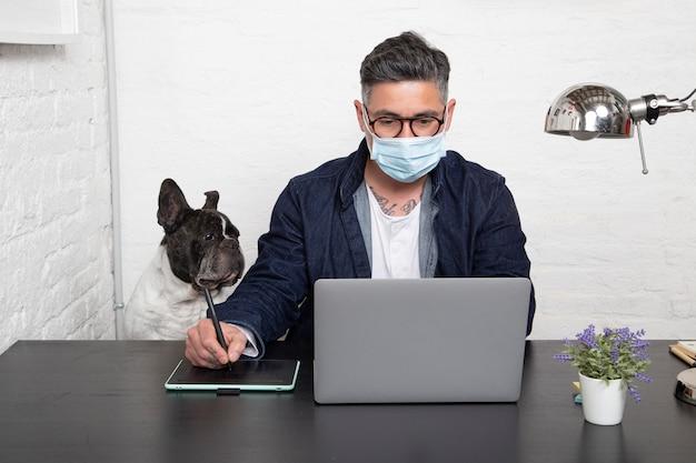 Mężczyzna w masce medycznej pracujący nad kreatywnym projektem z domu z psem siedzącym razem w obszarze roboczym.