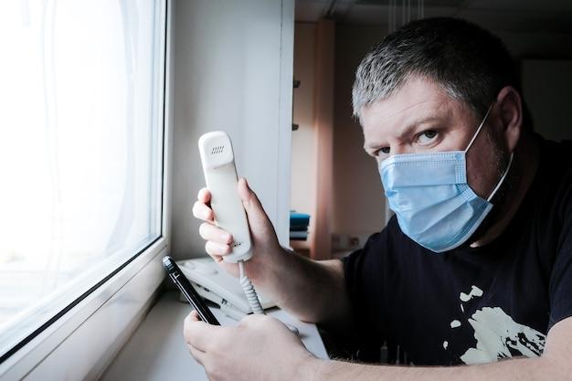 Mężczyzna w masce medycznej przed oknem trzyma w rękach telefon