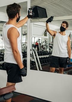 Mężczyzna w masce medycznej robi selfie na siłowni