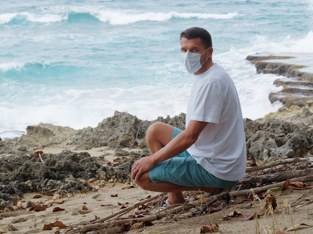 Mężczyzna w masce medycznej samotnie ustawiony na plaży rafy w letni dzień.