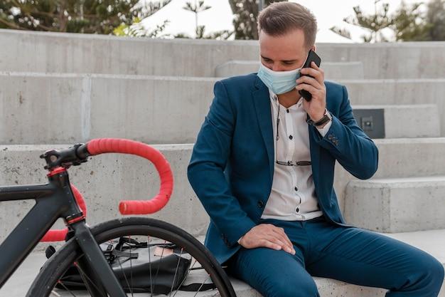 Mężczyzna w masce medycznej siedząc obok swojego roweru