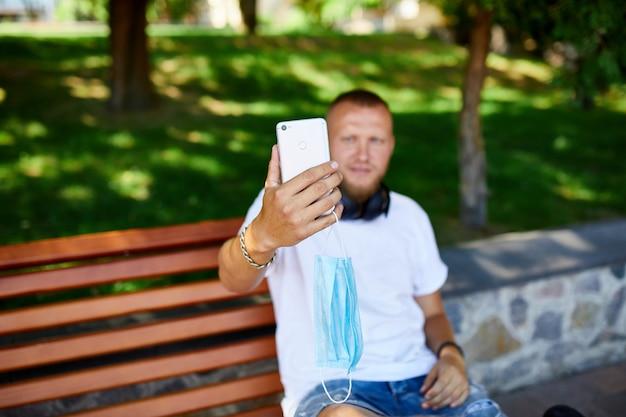 Mężczyzna w masce medycznej siedzi na ławce w parku robienie selfie przez telefon komórkowy