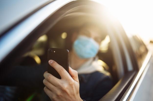 Mężczyzna w masce medycznej trzyma w ręku telefon komórkowy podczas prowadzenia samochodu