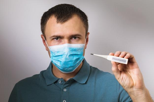 Mężczyzna w masce medycznej trzymający w ręku termometr