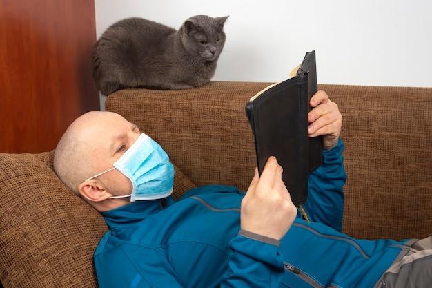 Mężczyzna w masce medycznej w domu poddany kwarantannie z powodu epidemii koronawirusa czyta biblię siedzącą na sofie obok szarego kota