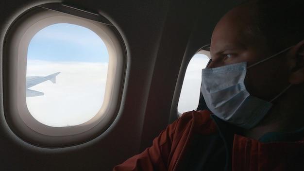 Mężczyzna w masce medycznej wygląda przez okno samolotu. zasady bezpieczeństwa podczas epidemii koronawirusa. podróżowanie podczas pandemii. 4k uhd