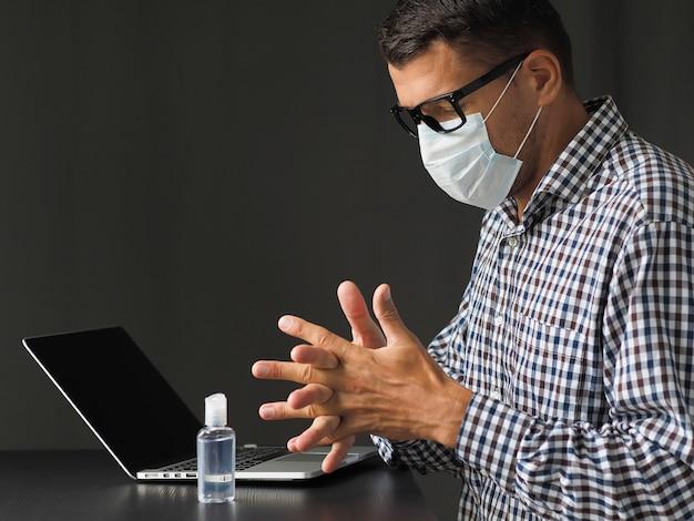 Mężczyzna w masce medycznej za pomocą alkoholu żel do dezynfekcji rąk po pracy z klawiaturą laptopa. koronawirus kwarantanny. praca w domu. bądź bezpieczny.