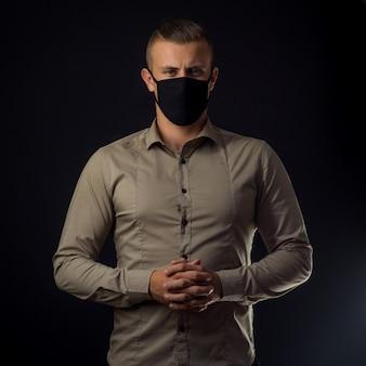 Mężczyzna w masce na czarnej ścianie