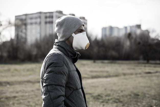 Mężczyzna w masce na ulicy. ochrona przed wirusami i przyczepnością