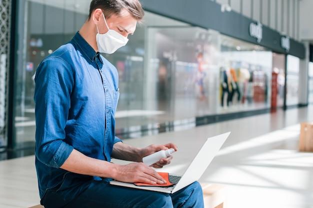 Mężczyzna w masce ochronnej dezynfekuje laptopa. pandemia w mieście