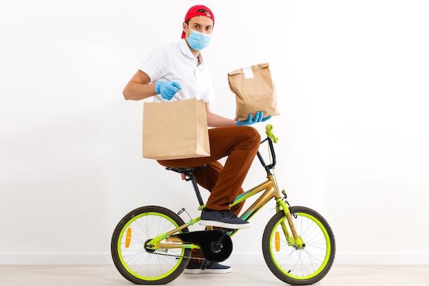 Mężczyzna w masce ochronnej dostarcza jedzenie na rowerze. zakupy online i dostawa ekspresowa. kwarantanna
