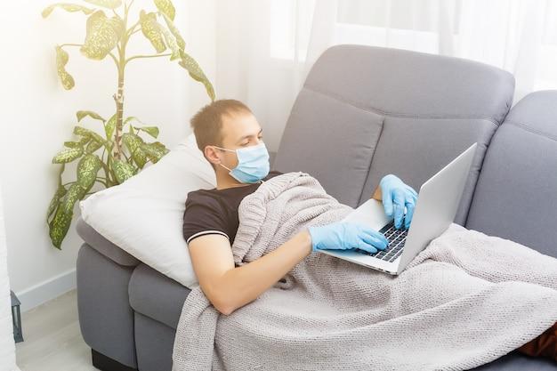 Mężczyzna w masce ochronnej leży w łóżku i pracuje na laptopie w domu. nowy koronawirus 2019-ncov z chin