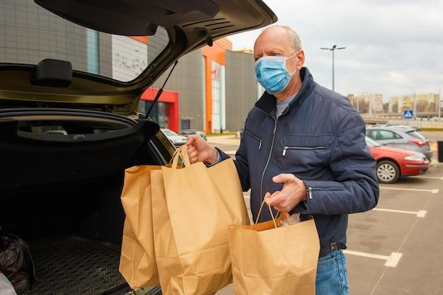 Mężczyzna w masce ochronnej na twarzy ładuje do samochodu paczki żywnościowe