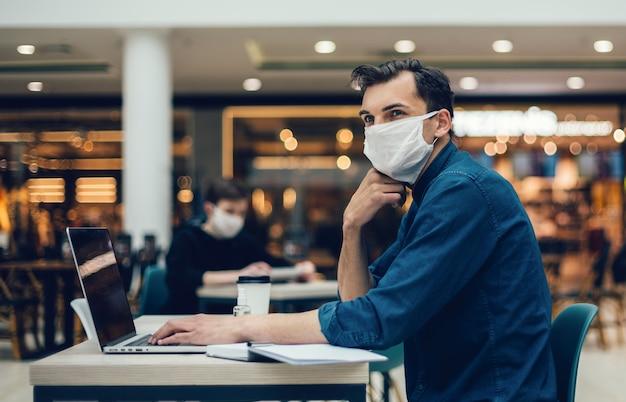 Mężczyzna w masce ochronnej pracuje na laptopie siedząc przy stoliku w kawiarni. zdjęcie z miejscem na kopię
