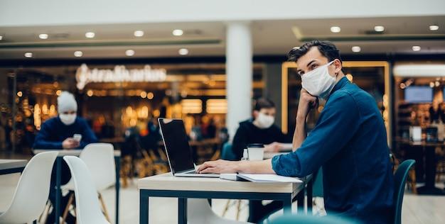 Mężczyzna w masce ochronnej pracuje na laptopie siedząc przy stoliku w kawiarni. zdjęcie z przestrzenią do kopiowania