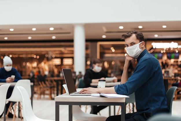 Mężczyzna w masce ochronnej pracuje na laptopie siedząc przy stoliku w kawiarni